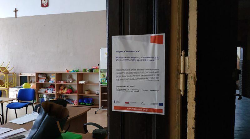 """Na zdjęciu po prawej stronie widać drzwi, na których przyklejony jest plakat z informacjami dotyczącymi projektu """"Kierunek Praca"""" a po lewej stronie widać salę, otwartą damską torebkę, stoliki, kartki, krzesła oraz meble z książkami i zabawkami."""